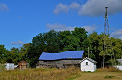 Neglected Farmstead falling to ruins. An old neglected farmstead is falling into ruins as the barn is giving indication of crumbling Royalty Free Stock Photography