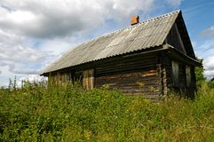 Neglected House. Closed house in the country with walled in windows and overgrown with grass and weeds stock image