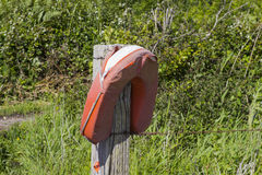 A neglected life saving buoyancy aid at a small footbridge on the Solent Way beach path on Southampton Water near Titchfield Commo. A dangerously neglected life Royalty Free Stock Photography