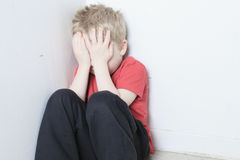 Neglected lonely child leaning at the wall Stock Photos