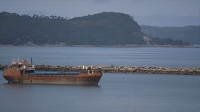 Neglected ocean carrier near stones jetty, Conakry. A wide steady shot of a rusty brown and white painted neglected vessel afloat, close to port`s stones jetty stock video footage