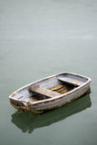 Neglected old rowing boat on calm sea water Royalty Free Stock Photo