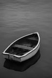 Neglected old rowing boat on calm sea water Royalty Free Stock Photos