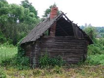 Neglected house. Neglected rural made of logs house with a tumbledown roof Royalty Free Stock Images
