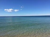 Negligenciando um grande lago com árvores e areia embaixo fotografia de stock royalty free