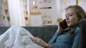 Negociações da jovem mulher no telefone celular em um sofá filme