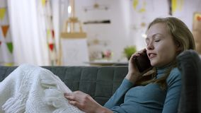 Negociações da mulher no smartphone em um sofá video estoque