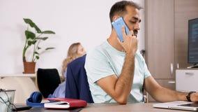 Negociações do homem no telefone e tipos no computador quando sua amiga jogar um jogo de vídeo no backgorund vídeos de arquivo