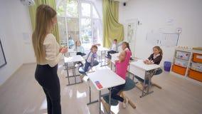 Negociações fêmeas do professor novo às crianças pequenas bonitos dos eruditos em mesas durante a lição de ensino na sala de aula filme