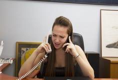 Negociações nervosas de uma menina a duas linhas telefônicas imagem de stock
