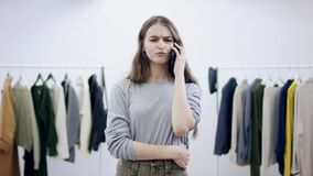 Negociaciones bonitas de mujer joven sobre el teléfono móvil en un cuarto de la ropa metrajes