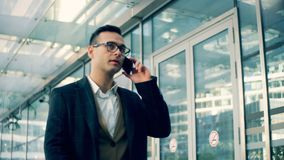 Negociaciones corporativas ocupadas sobre un teléfono en una calle, cierre del encargado para arriba