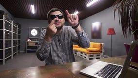 Negociaciones de las gafas de sol del hombre que llevan joven en la cámara y muestras el mostrar con sus fingeres almacen de metraje de vídeo