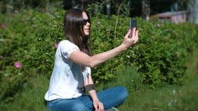 Negociaciones del blogger de la mujer sobre la charla video, tirándose en un teléfono móvil, vídeo del selfie almacen de metraje de vídeo