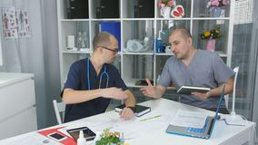 Negociaciones del doctor de la clínica de la oficina del doctor a un colega La reunión con el jefe almacen de metraje de vídeo