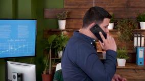 Negociaciones del hombre de negocios sobre el teléfono mientras que camina en la oficina almacen de video