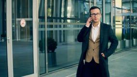 Negociaciones del hombre de negocios sobre un teléfono móvil en un centro de negocios, cierre para arriba