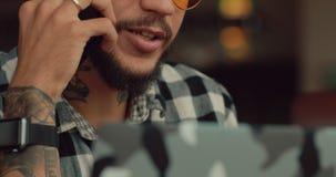 Negociaciones del hombre por el smartphone que se sienta en el café, comunicación empresarial
