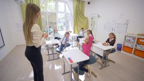 Negociaciones femeninas del educador joven a los pequeños niños lindos de los escolares en los escritorios durante la lección de  metrajes