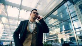 Negociaciones masculinas corporativas del encargado sobre un teléfono móvil, caminando en una calle, cierre para arriba