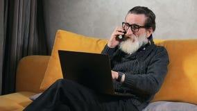 Negociaciones mayores del hombre sobre el teléfono antes del ordenador portátil metrajes