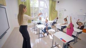 Negociaciones profesionales de la mujer del profesor a los pequeños alumnos lindos de los niños en los escritorios durante la lec metrajes