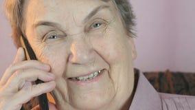 Negociaciones sonrientes envejecidas de la mujer 80s sobre el teléfono móvil metrajes