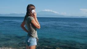 Negociaciones turísticas de la muchacha sobre el teléfono en las vacaciones en la isla tropical, cámara lenta almacen de video