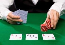 Negociante de Holdem com cartões de jogo e microplaquetas do casino Fotografia de Stock