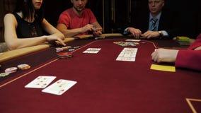 Negociante do casino que põe cartões sobre a tabela vermelha, jogo de pôquer, jogando, mãos do close-up Jogadores no fundo filme