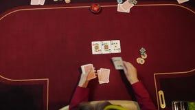 Negociante do casino que põe cartões sobre a tabela vermelha, jogo de pôquer, jogando, mãos do close-up Vista superior filme
