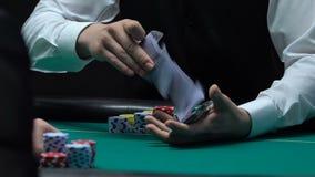 Negociante do pôquer que baralha masterfully cartões, negócio do entretenimento do casino, lento-mo filme