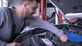 Negocio automovilístico, coche de las reparaciones del hombre del mecánico con una capilla abierta en el trabajo en coche de las  almacen de video