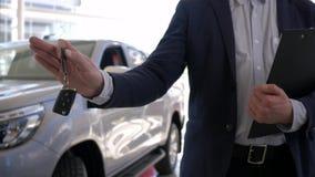 Negocio automovilístico, controles jovenes del vendedor en llaves de los brazos al nuevo coche en venta en centro de ventas metrajes
