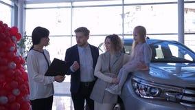 Negocio automovilístico, familia feliz de las compras con poca hija consultada con la dependienta sobre el coche de compra en la  almacen de video