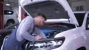 Negocio automovilístico, retrato del técnico sonriente atractivo durante la reparación del coche con la capilla abierta en la gas almacen de metraje de vídeo