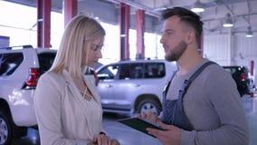 Negocio automovilístico, señora del dueño e individuo del técnico hablando sobre mantenimiento del coche en la gasolinera almacen de video