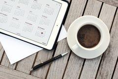 Negocio, calendarios, cita Tabla de la oficina con la libreta, ordenador, taza de café Imagen de archivo libre de regalías