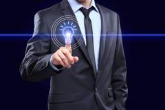 Negocio, concepto de la tecnología - hombre de negocios que presiona el botón con el bulbo en las pantallas virtuales Imágenes de archivo libres de regalías