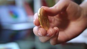Negocio del cryptocurrency del mundo Mano de la mujer que sostiene la moneda del bitcoin del oro almacen de video