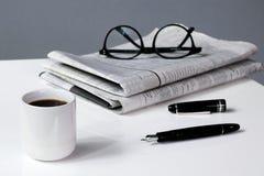 Negocio del descanso para tomar café con la pluma y los vidrios del periódico Foto de archivo libre de regalías