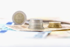 Negocio, finanzas, inversión, ahorro y concepto del efectivo - cercano para arriba de los billetes y de las monedas euro en la ta Foto de archivo libre de regalías
