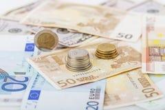 Negocio, finanzas, inversión, ahorro y concepto del efectivo - cercano para arriba de los billetes y de las monedas euro en la ta Imágenes de archivo libres de regalías