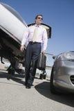 Negocio maduro que camina en el campo de aviación Fotografía de archivo libre de regalías