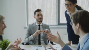 Negocio masculino y colegas femeninos que ríen mientras que habla durante la rotura que se sienta en la tabla en oficina moderna metrajes