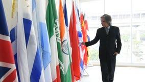 Negocio o tacto político del hombre las banderas internacionales y caminar a través para tocar todos los pedazos metrajes