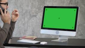 Negocio, plazo y concepto de la tecnología - hombre con el ordenador que invita a smartphone y que señala al monitor Verde almacen de video