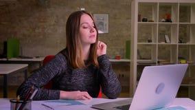 Negocio que conduce de la mujer caucásica joven usando vieochat en su ordenador portátil en oficina almacen de video