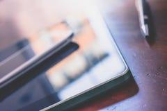 Negocio Smartphone y tableta con la reflexión al lado de un Biro en la tabla de madera fotografía de archivo libre de regalías