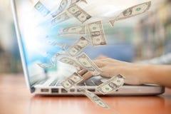 Negocio un negocio en línea del ordenador portátil que hace billetes de dólar del dinero Fotos de archivo